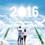 Escaleras que suben de la familia feliz hacia los números 2016 Imagen de archivo libre de regalías