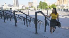 Escaleras que suben de la mujer asiática a toda prisa para el trabajo metrajes
