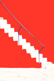 Escaleras rendidas en la pared roja Foto de archivo
