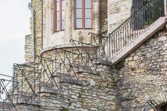 Escaleras viejas, de piedra en el lado del edificio con hierro labrado Foto de archivo