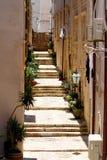 Escaleras viejas en edificios estrechos de la piedra del camino Imagen de archivo libre de regalías