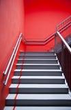 Escaleras y pared roja Fotos de archivo