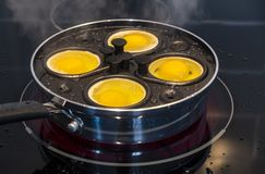 Escalfar cuatro huevos para el desayuno en una cacerola Huevo-que escalfa 1 fotos de archivo libres de regalías