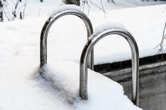 Escalier en métal dans la piscine extérieure couverte de neige images stock