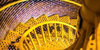 Escalier en spirale jaune avec les bandes de roulement treillagées vers le bas image libre de droits