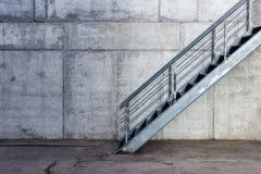 Escalier métallique sur le fond du mur gris de ciment images libres de droits