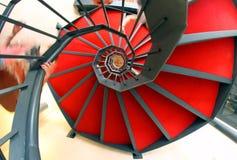 Escalier spiralé avec du tapis rouge Photos libres de droits
