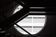 Escaliers avec la fenêtre ronde dans l'obscurité Images libres de droits