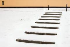 escaliers couverts de neige au mur du bâtiment jaune avec la fenêtre Images libres de droits