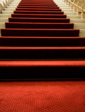 Escaliers couverts du tapis rouge Photographie stock