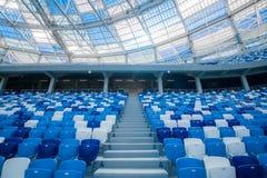 Escaliers de ciment et sièges bleus à l'intérieur de stade de football Photos libres de droits