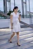 Escaliers de marche de dame d'affaires avec les genoux de téléphone portable Photo libre de droits