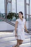 Escaliers de marche de dame d'affaires avec les genoux de téléphone portable Photographie stock libre de droits