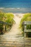 Escaliers en bois au-dessus des dunes à la plage Photographie stock libre de droits