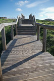 Escaliers en bois de voie montant en rebord vert scénique de côte atlantique en ciel bleu Photo stock