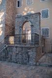 Escaliers en pierre antiques avec l'entrée arquée Photographie stock libre de droits