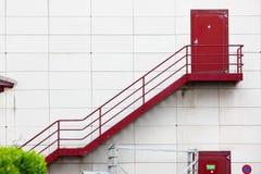 Escaliers extérieurs et porte rouge Photo libre de droits