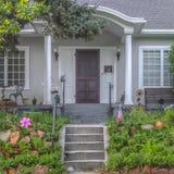 Escaliers menant au porche et à la porte brune d'une maison photos stock