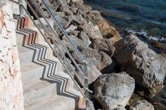 Escaliers par la mer Méditerranée avec les roches et le modèle d'ombre de zigzag Photo stock