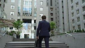 Escaliers s'élevants d'homme occupé, plantes vertes entourées par la ville écologique de murs en pierre clips vidéos