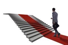 Escaliers s'élevants de jeune homme d'affaires et tapis rouge sur le backgr blanc Photographie stock libre de droits
