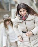 Escaliers s'élevants de sourire de jeune femme avec l'ami dehors Image libre de droits
