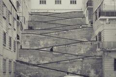 Escaliers urbains entre les bâtiments, deux rues de niveaux, trois villes Images libres de droits