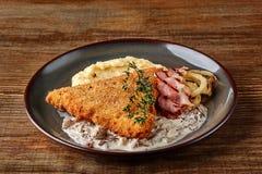 Escalope de veau de poulet avec l'herbe, la purée de pommes de terre et la sauce aux champignons du plat sur le fond en bois de t Photo libre de droits