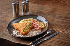 Escalope de veau de poulet avec l'herbe, la purée de pommes de terre et la sauce aux champignons du plat sur le fond en bois de t Image stock