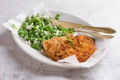 Escalope del pollo o del cerdo con queso y ensalada de los guisantes fotos de archivo