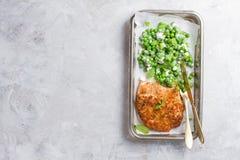 Escalope del pollo o del cerdo con queso y ensalada de los guisantes imagenes de archivo