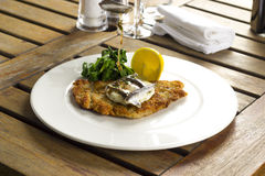 Escalope of veal Holstein with spinach, lemon Royalty Free Stock Photo