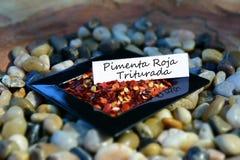 Escamas de pimienta roja en un pequeño plato con la etiqueta del español Imagen de archivo libre de regalías