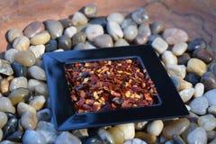 Escamas de pimienta roja machacadas en un pequeño plato Imágenes de archivo libres de regalías
