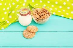 Escamas y galletas de la avena con el jarro de leche en cocina de madera azul Mantel en lunares Copy space and selective focus Fotografía de archivo libre de regalías