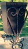 Escaninho de lixo com o ferro que forja em um parque da recrea??o foto de stock