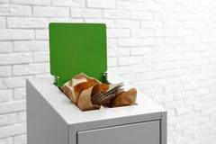Escaninho de lixo com papel e cartão perto da parede, espaço para o texto Reciclando o conceito imagens de stock