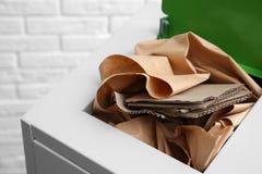 Escaninho de lixo com papel e cartão perto da parede de tijolo Reciclando o conceito fotografia de stock royalty free