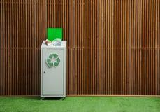 Escaninho de lixo enchido em demasia com reciclagem do símbolo perto da parede dentro Espaço para o texto fotos de stock royalty free