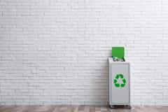 Escaninho de lixo enchido em demasia com reciclagem do símbolo perto da parede dentro Espaço para o texto imagem de stock royalty free