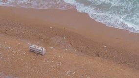 Escantillones blancos de madera solos en una playa arenosa almacen de metraje de vídeo
