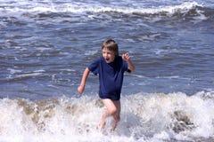 Escapando as ondas Fotos de Stock Royalty Free