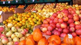 Escaparate con el caqui, las manzanas, las peras, las granadas y diversa fruta en el mercado callejero almacen de video