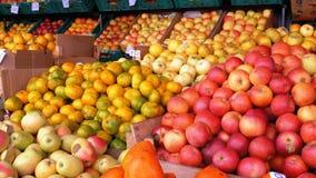 Escaparate con las mandarinas, las manzanas, las peras, el caqui y diversa fruta en el mercado callejero almacen de video