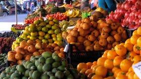 Escaparate con las peras, el caqui, las manzanas, las granadas y diversa fruta en el mercado callejero almacen de video