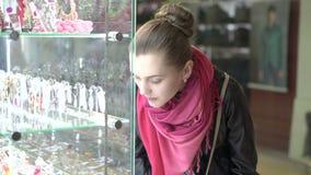 Escaparate de examen de la muchacha bonita de joyas en centro comercial 4K metrajes