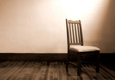 Escape. Wooden chair alone in a room lit by only a window Stock Images