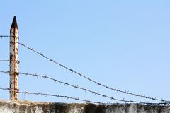 Escape. Weighed down barbed wire against the sky Royalty Free Stock Photos