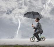 Escape from crisis. Concept of escape from crisis with businessman on bike stock photography