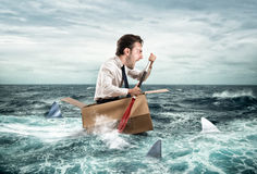Escape from crisis. Funny face. Fearful Businessman escapes screaming from sharks on a cardboard. Funny face Stock Images